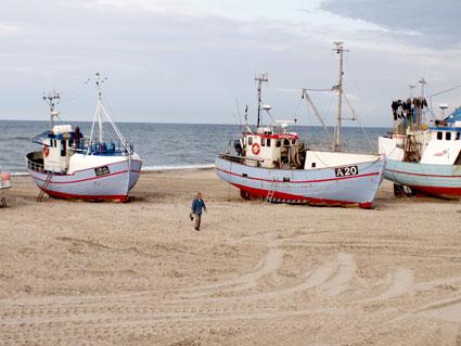 Kurt Mortensen ser på fiskekuttere trukket op på stranden i Torup.